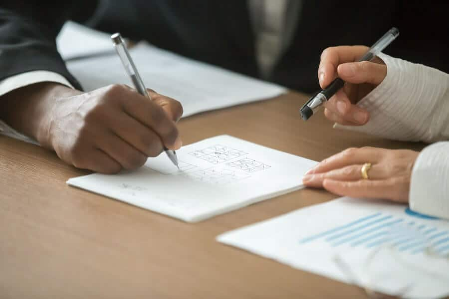 Two people analyzing handwritten notes on desk
