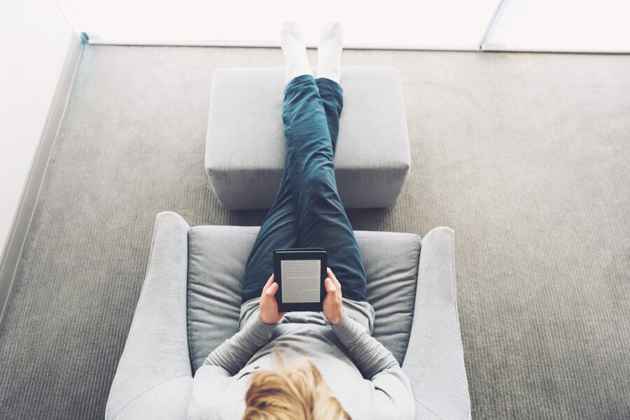 bird's eye view of person sitting in recliner reading on tablet
